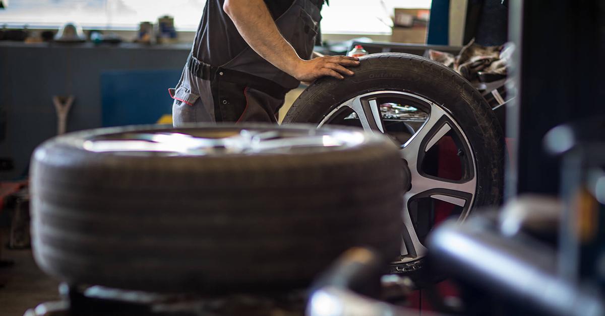 automechanik v servise mera hlbku dezenu na pneumatikach